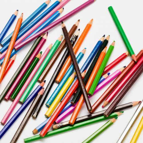 Many pencils different colours on white background
