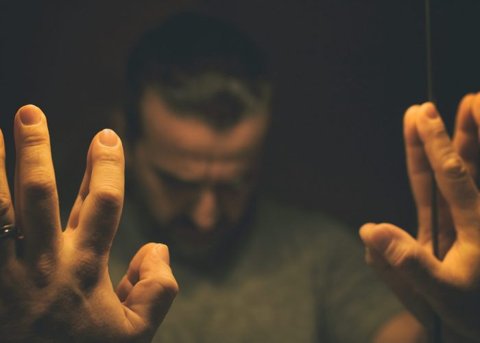Man in despair with raised hands and bowed hand, in a low light room looking in front of mirror